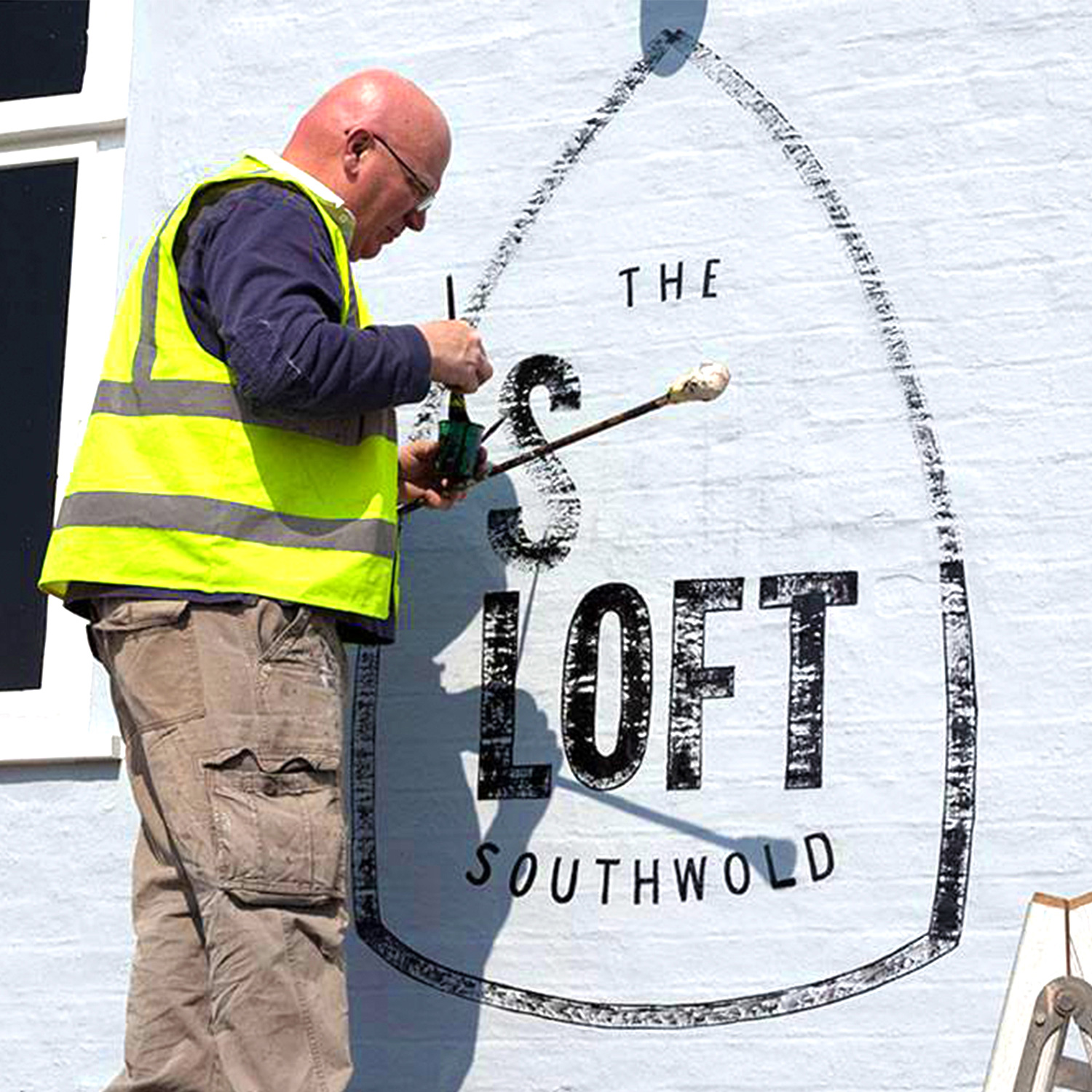 Sail Loft sign being painted on the wall