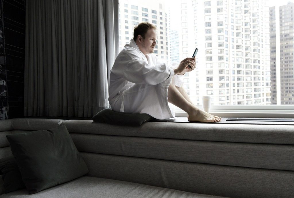 Man sitting on a windowsill with a phone in his hand